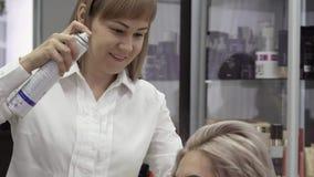 Cabeleireiro Makes Professional Styling da mulher com um pulverizador filme