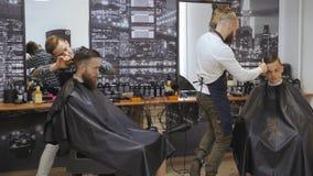 Cabeleireiro para homens barbershop Inquietação com a barba O barbeiro com tosquiadeira de cabelo trabalha no penteado para o ind video estoque