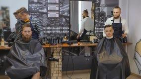 Cabeleireiro para homens barbershop Inquietação com a barba O cabeleireiro com um corte de cabelo trabalha para um penteado para  filme