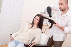 Cabeleireiro profissional com o secador de cabelo no salão de beleza fotografia de stock