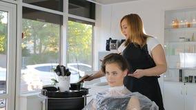 Cabeleireiro profissional, estilista que colore o cabelo adolescente da menina video estoque