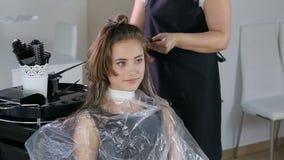 Cabeleireiro profissional, estilista que colore o cabelo adolescente da menina vídeos de arquivo