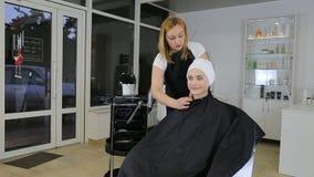Cabeleireiro profissional, estilista que prepara a menina adolescente para hairdress vídeos de arquivo