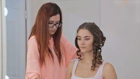 Cabeleireiro profissional que faz o penteado para a mulher bonita nova video estoque