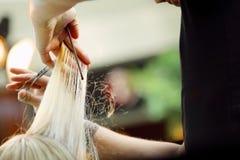 Cabeleireiro que apara o cabelo louro com tesouras Foto de Stock Royalty Free