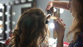 Cabeleireiro que faz o envoltório que ondula o cabelo marrom em um salão de beleza com ferro filme