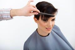 Cabeleireiro que faz o penteado Morena com cabelo curto no salão de beleza imagem de stock royalty free