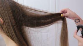 Cabeleireiro que faz o penteado para a mulher bonita nova e que usa o pulverizador de cabelo video estoque