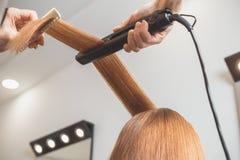 Cabeleireiro que faz um penteado para o cliente imagem de stock
