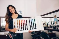 Cabeleireiro que mostra o cartão da máscara da cor do cabelo no salão de beleza imagem de stock