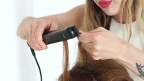 Cabeleireiro que ondula usando tenazes de brasa do cabelo perto acima Processe a ondulação com ferro do cabelo no estúdio da bele vídeos de arquivo
