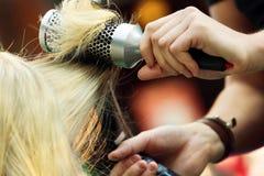 Cabeleireiro que penteia o cabelo da moça por seco da escova de cabelo e de cabelo Imagens de Stock Royalty Free