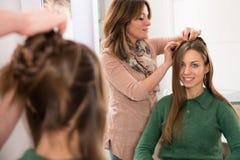 Cabeleireiro que penteia um corte de cabelo à moça imagem de stock royalty free