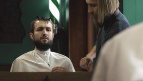 Cabeleireiro que prepara-se para um corte de cabelo paciente do ` s no barbeiro video estoque
