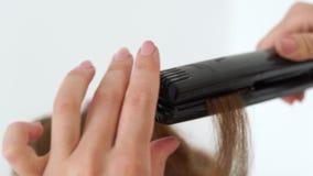 Cabeleireiro que usa tenazes de brasa do cabelo para o fim de ondulação acima Processe o cabelo longo de ondulação com ferro no e video estoque