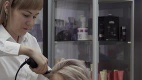 Cabeleireiro sociável Makes Beautiful Curls da jovem mulher vídeos de arquivo