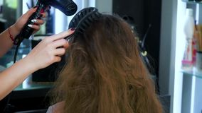 Cabello seco del peluquero con el pelo largo, ondulado, rubio almacen de video