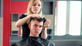 Cabello seco del peluquero profesional en salón de belleza metrajes