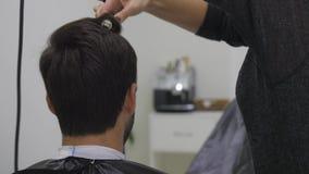 Cabello seco del peluquero profesional en salón de belleza Cliente joven masculino y peluquero de sexo femenino Cierre para arrib almacen de video