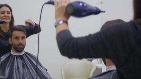 Cabello seco del peluquero profesional en salón de belleza Cliente joven masculino y peluquero de sexo femenino Cierre para arrib metrajes