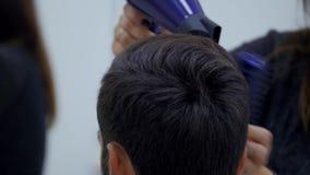 Cabello seco del peluquero profesional en salón de belleza Cliente joven masculino y peluquero de sexo femenino Cierre para arrib almacen de metraje de vídeo