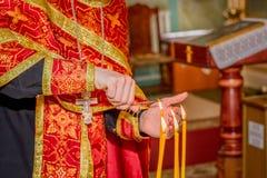 Cabelo ardente da mão do padre na luz da vela Fotografia de Stock Royalty Free