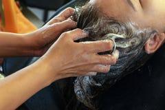 Cabelo asiático do cliente da lavagem da mulher com champô no cabeleireiro Beauty Salon imagem de stock