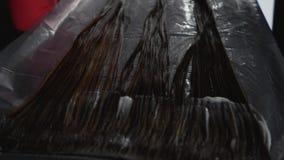 Cabelo da cor do cabeleireiro O cabeleireiro do estilista faz a coloração de cabelo Mãos do ` s do cabeleireiro em luvas pretas b filme