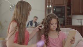 Cabelo de escovadela da mãe nova de sua filha no primeiro plano quando pai e filho que jogam no portátil no fundo vídeos de arquivo