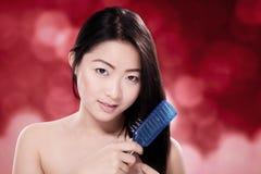 Cabelo de escovadela da mulher chinesa bonita contra o fundo vermelho borrado Fotografia de Stock