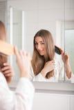 Cabelo de escovadela da mulher nova na frente do espelho Fotografia de Stock