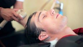 Cabelo de lavagem do barbeiro ao homem considerável novo no salão de beleza masculino Cliente no salão de beleza do barbeiro 1920 filme