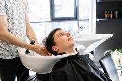 Cabelo de lavagem do cabeleireiro a seu cliente considerável Barbeiro no trabalho Homem no barbeiro imagens de stock royalty free