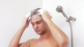 Cabelo de lavagem do homem novo sob o chuveiro O homem lava seu cabelo em casa filme