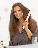 Cabelo de ondulação da jovem mulher com straightener Imagem de Stock Royalty Free