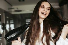 Cabelo de secagem alegre novo da mulher com blowdryer fotografia de stock