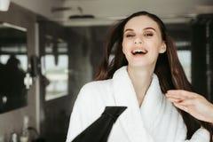 Cabelo de secagem alegre novo da mulher com blowdryer imagem de stock royalty free