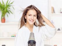 Cabelo de secagem da mulher em casa Fotografia de Stock