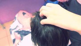 Cabelo de secagem do barbeiro com secador de cabelo Close-up do cabelo Reforçando o cabelo com queratina video estoque