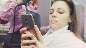Cabelo de secagem do barbeiro com secador de cabelo Reforçando o cabelo com queratina O cliente olha o telefone celular vídeos de arquivo