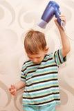 Cabelo de secagem do rapaz pequeno com secador de cabelo. Imagem de Stock