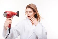 Cabelo de secagem surpreendido da jovem mulher bonita e vista do secador interno Fotografia de Stock Royalty Free