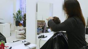 Cabelo do corte da jovem mulher no cabeleireiro O barbeiro corta o cabelo a uma moça com tesouras profissionais video estoque