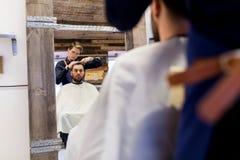 Cabelo do corte do homem e do barbeiro no barbeiro Fotografia de Stock