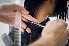 Cabelo do ` s do cliente do corte do cabeleireiro no salão de beleza com close up das tesouras Usando um pente fotos de stock