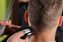 Cabelo dos clientes do corte do cabeleireiro com uma tosquiadeira de cabelo elétrica fotografia de stock