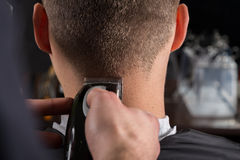Cabelo dos clientes do corte do cabeleireiro com uma tosquiadeira de cabelo elétrica imagem de stock