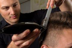 Cabelo dos clientes do corte do cabeleireiro com uma tosquiadeira de cabelo elétrica Fotografia de Stock Royalty Free