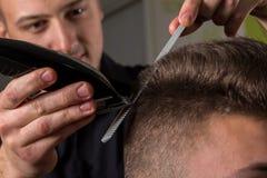 Cabelo dos clientes do corte do cabeleireiro com uma tosquiadeira de cabelo elétrica fotos de stock royalty free
