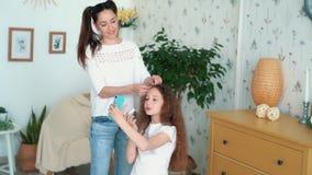 Cabelo dos pentes e das tranças da mãe da filha na trança, movimento lento